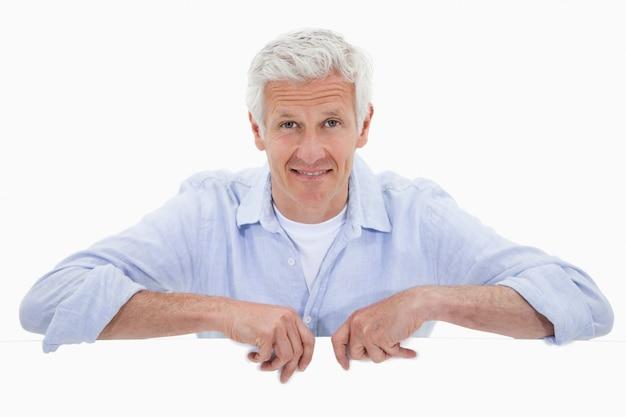 Portrait d'un homme d'âge mûr souriant, debout derrière le panneau vierge