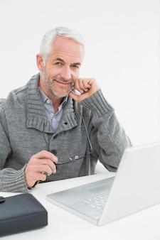 Portrait d'un homme d'âge mûr souriant avec un ordinateur portable au bureau