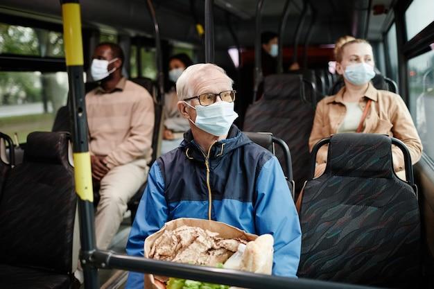 Portrait d'un homme âgé portant un masque dans un bus lors d'un voyage en transports en commun en ville, espace pour copie