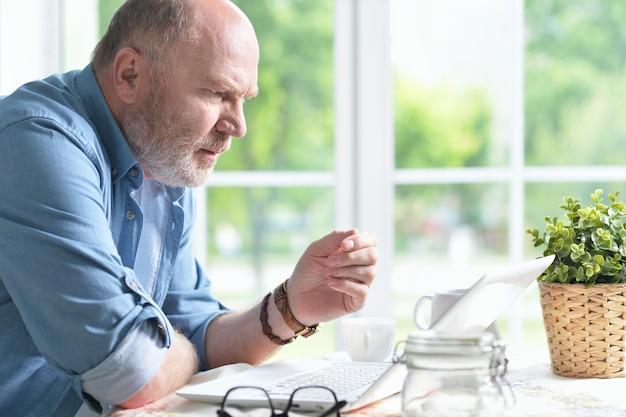 Portrait d'un homme âgé utilisant un ordinateur portable