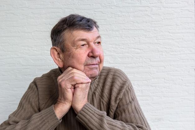 Portrait d'un homme âgé, vieux senior croisé les mains ridées.