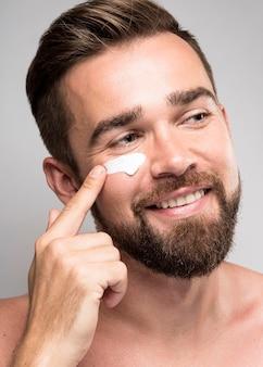 Portrait d'homme à l'aide de crème pour le visage