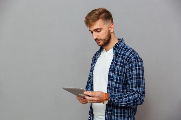 Portrait d'un homme à l'aide d'un ordinateur tablette isolé sur un mur gris