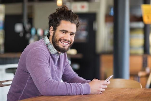 Portrait d'homme à l'aide de téléphones mobiles alors qu'il était assis au restaurant