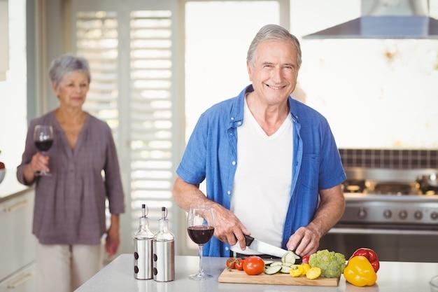 Portrait, homme aîné, couper légumes, à, femme, dans, fond