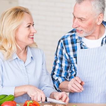 Portrait, homme aîné, regarder, femme, couper, champignon, à, couteau, table