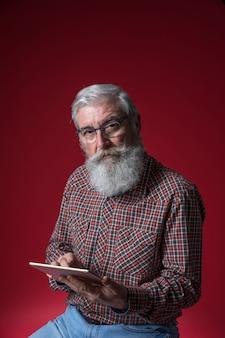 Portrait, de, a, homme aîné, tenant tablette numérique, dans main, regarder, à, appareil photo, contre, toile de fond rouge