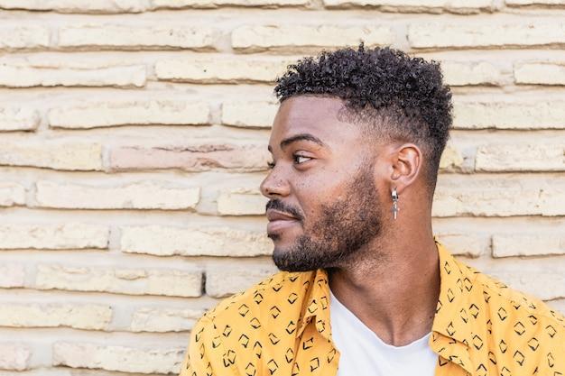 Portrait d'un homme américain attrayant avec barbe et un piercing portant une chemise jaune dans un mur de briques