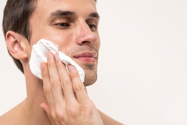 Portrait d'un homme appliquant de la mousse à raser