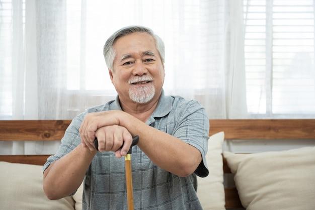 Portrait d'un homme asiatique âgé âgé s'asseoir sur la main de l'entraîneur tenir le bâton de marche regarder la caméra avec le sourire.