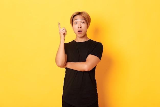Portrait d'un homme asiatique beau réfléchi, levant le doigt