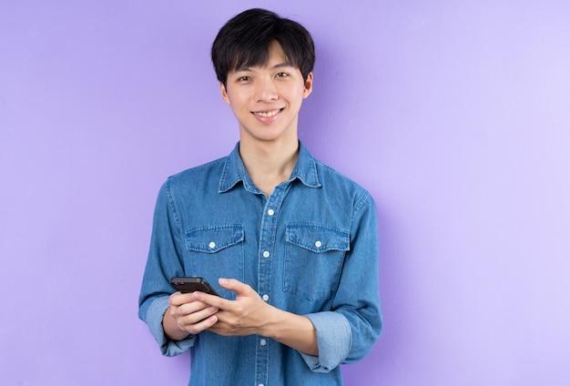 Portrait d'un homme asiatique en chemise bleue posant sur fond violet
