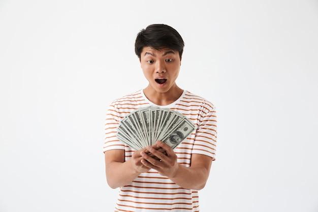 Portrait d'un homme asiatique choqué tenant de l'argent