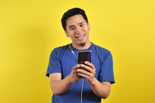 Portrait d'un homme asiatique excité surpris de trouver une chanson tendance en ligne