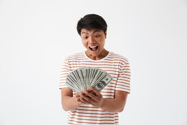 Portrait d'un homme asiatique excité tenant des billets d'argent
