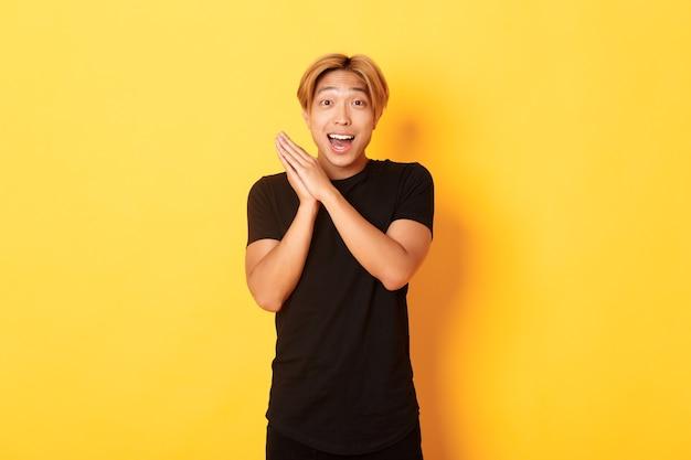Portrait d'homme asiatique heureux et surpris applaudir et souriant ravi