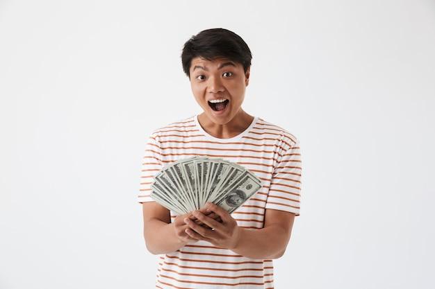Portrait d'un homme asiatique heureux tenant des billets d'argent
