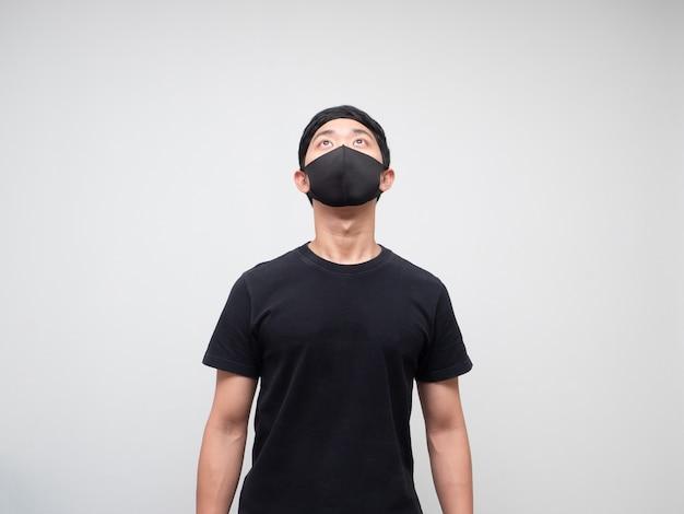 Portrait homme asiatique avec masque de protection regardant vers l'espace sur fond blanc