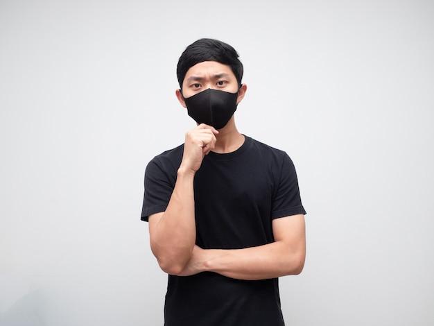 Portrait homme asiatique portant un masque de protection visage sérieux et pensant quelque chose sur fond de mur blanc