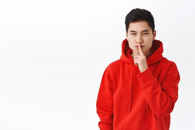 Portrait d'un homme asiatique sournois et beau en sweat à capuche rouge, garder le secret, plisser les yeux mystérieux et se taire, faire un geste de silence, doigt sur les lèvres, cacher quelque chose, préparer une surprise, mur blanc.