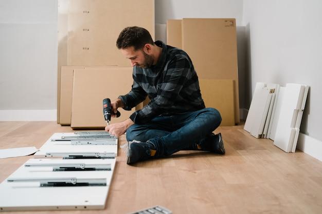 Portrait d'homme assemblant des meubles. faites-le vous-même l'assemblage de meubles.