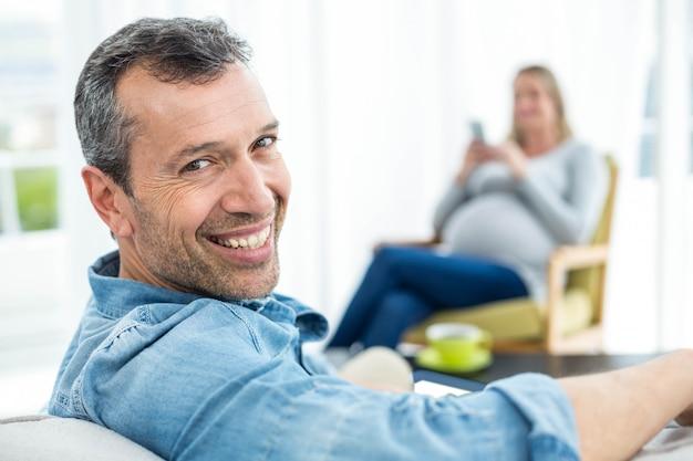 Portrait d'homme assis sur un canapé et souriant dans le salon