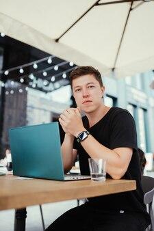 Portrait d'un homme assis à une table travaillant sur un ordinateur portable. vue de côté.
