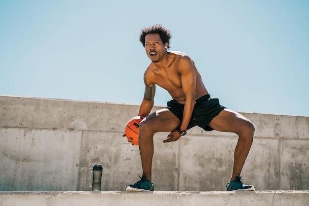 Portrait d'homme athlète afro jouant et pratiquant avec ballon de basket à l'extérieur. sport et mode de vie sain.