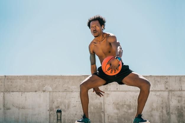 Portrait d'un homme athlète afro jouant et pratiquant avec un ballon de basket à l'extérieur. sport et mode de vie sain.