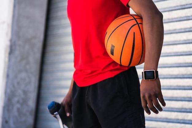 Portrait d'un homme athlète afro tenant un ballon de basket en se tenant debout à l'extérieur. sport et mode de vie sain.