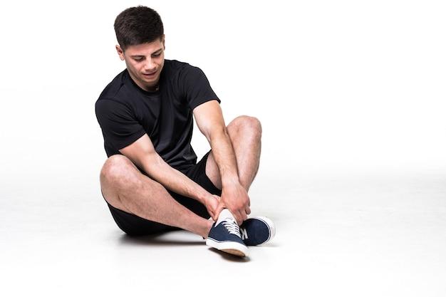 Portrait d'homme athlète souffrant de douleurs dans la jambe isolé sur un blanc