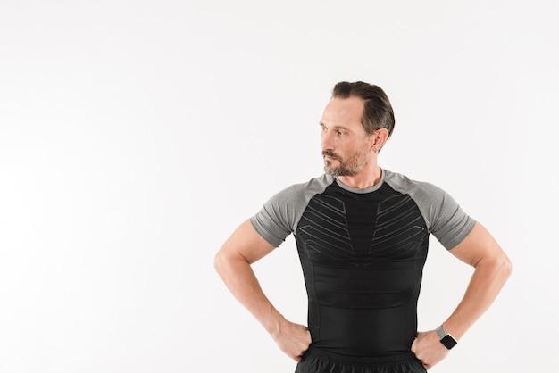 Portrait d'homme athlétique des années 30 portant des vêtements de sport à côté sur fond avec un regard concentré tout en pratiquant des sports,