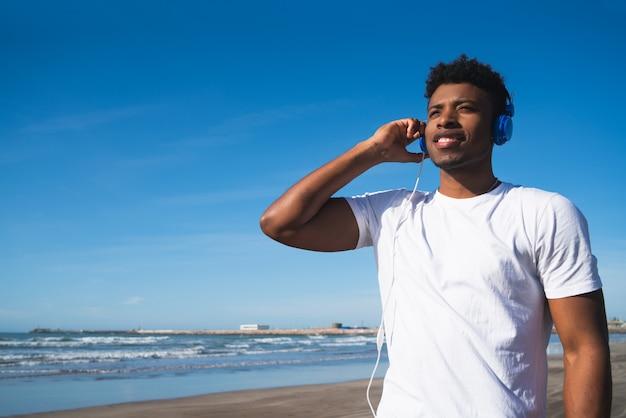 Portrait d'un homme athlétique écoutant de la musique avec des écouteurs tout en se reposant pour faire de l'exercice à la plage.