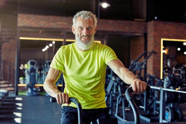 Portrait d'un homme athlétique mature épuisé en vêtements de sport faisant du vélo sur des vélos d'exercice à la salle de sport
