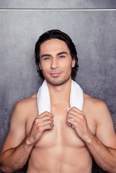 Portrait d'un homme athlétique nu heureux avec une serviette blanche