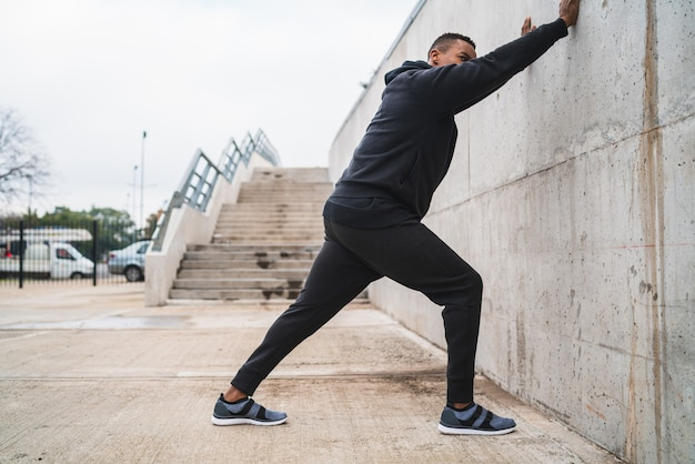 Portrait d'un homme athlétique qui s'étend des jambes avant de faire de l'exercice à l'extérieur. sport et mode de vie sain.