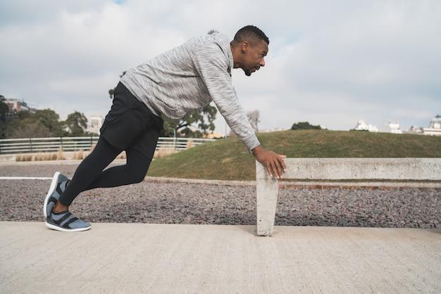 Portrait d'un homme athlétique qui s'étend des muscles avant de faire de l'exercice à l'extérieur. sport et mode de vie sain.