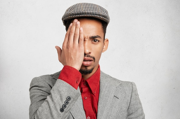 Portrait d'homme attrayant porte une casquette, une chemise rouge formelle avec une veste, couvre les yeux avec la main comme cache une grande ecchymose