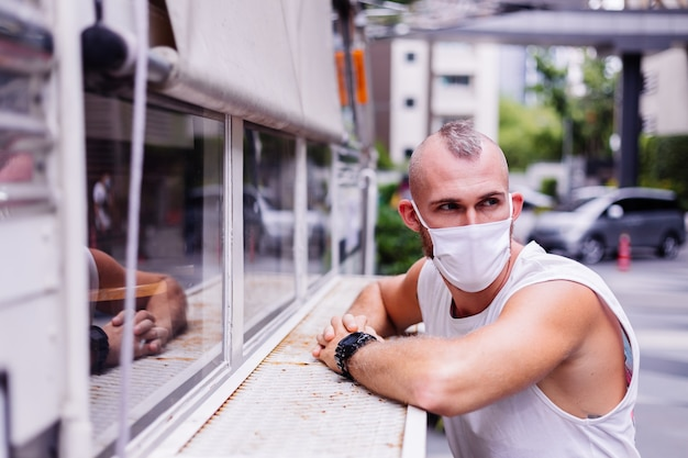 Portrait d'homme au masque médical blanc sur la place centrale de la ville est assis sur une chaise à van cafe