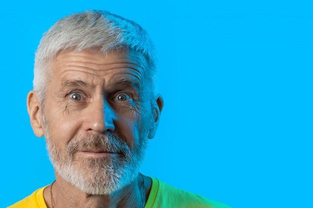 Portrait d'homme aux cheveux gris surpris et curieux avec une barbe sur un bleu