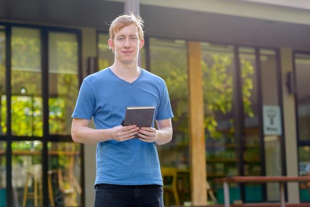 Portrait d'homme aux cheveux rouges dans le jardin à l'extérieur