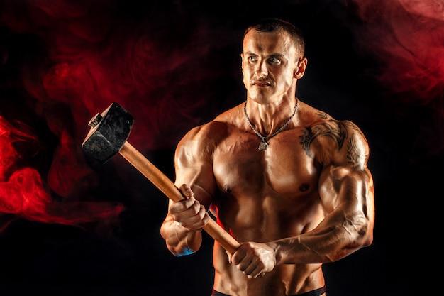 Portrait d'un homme aux seins nus musclé sérieux avec un marteau