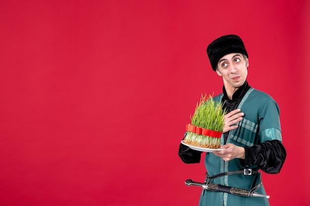 Portrait d'un homme azéri en costume traditionnel avec semeni sur les danseurs ethniques rouges du printemps novruz