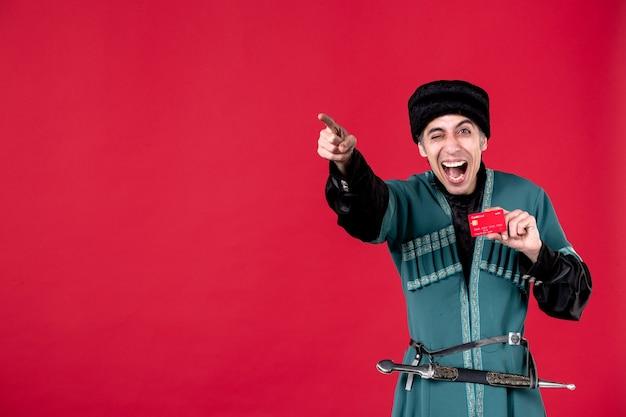 Portrait d'un homme azéri en costume traditionnel tenant une carte de crédit pointant en studio de l'argent rouge ethnique du printemps de novruz