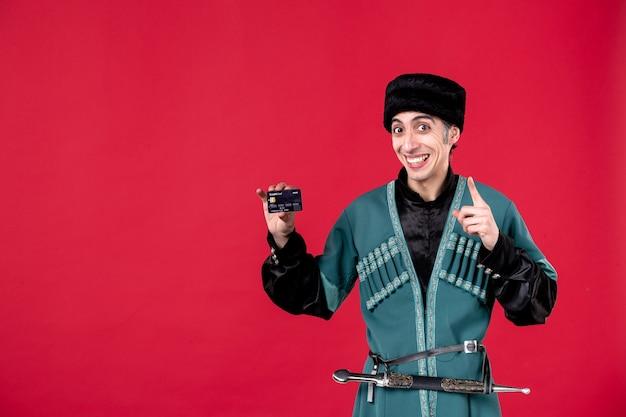 Portrait d'un homme azéri en costume traditionnel tenant une carte de crédit studio photo rouge ethnique novruz printemps argent photo