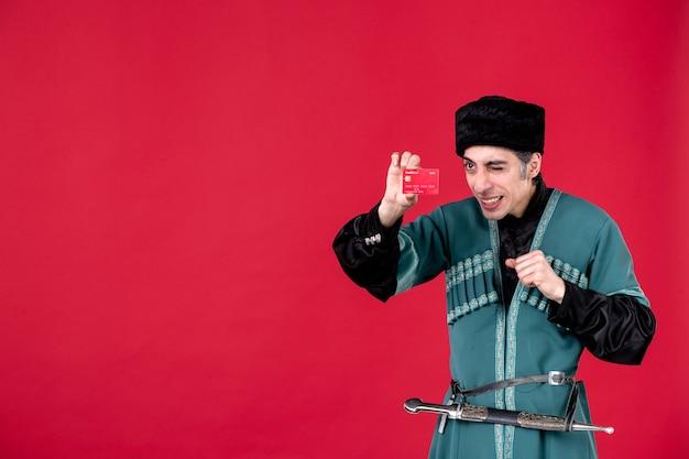 Portrait d'un homme azéri en costume traditionnel tenant une carte de crédit studio shot argent printemps ethnique rouge