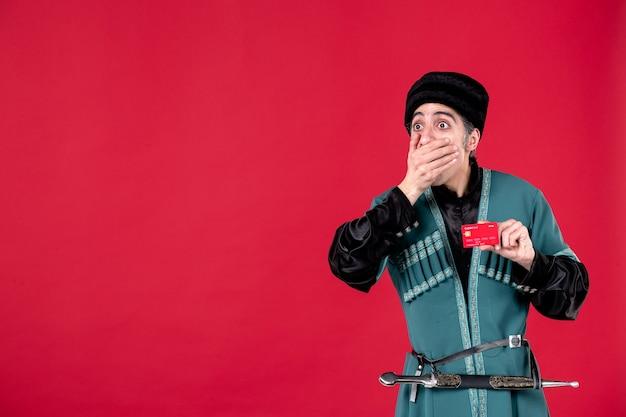 Portrait d'un homme azéri en costume traditionnel tenant une carte de crédit studio shot argent printemps rouge ethnique
