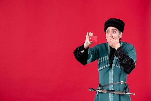 Portrait d'un homme azéri en costume traditionnel tenant une carte de crédit studio shot printemps ethnique rouge novruz
