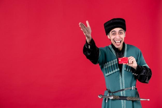 Portrait d'un homme azéri en costume traditionnel tenant une carte de crédit studio shot red novruz printemps argent