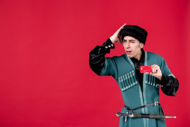 Portrait d'un homme azéri en costume traditionnel tenant une carte de crédit studio shot red spring money novruz